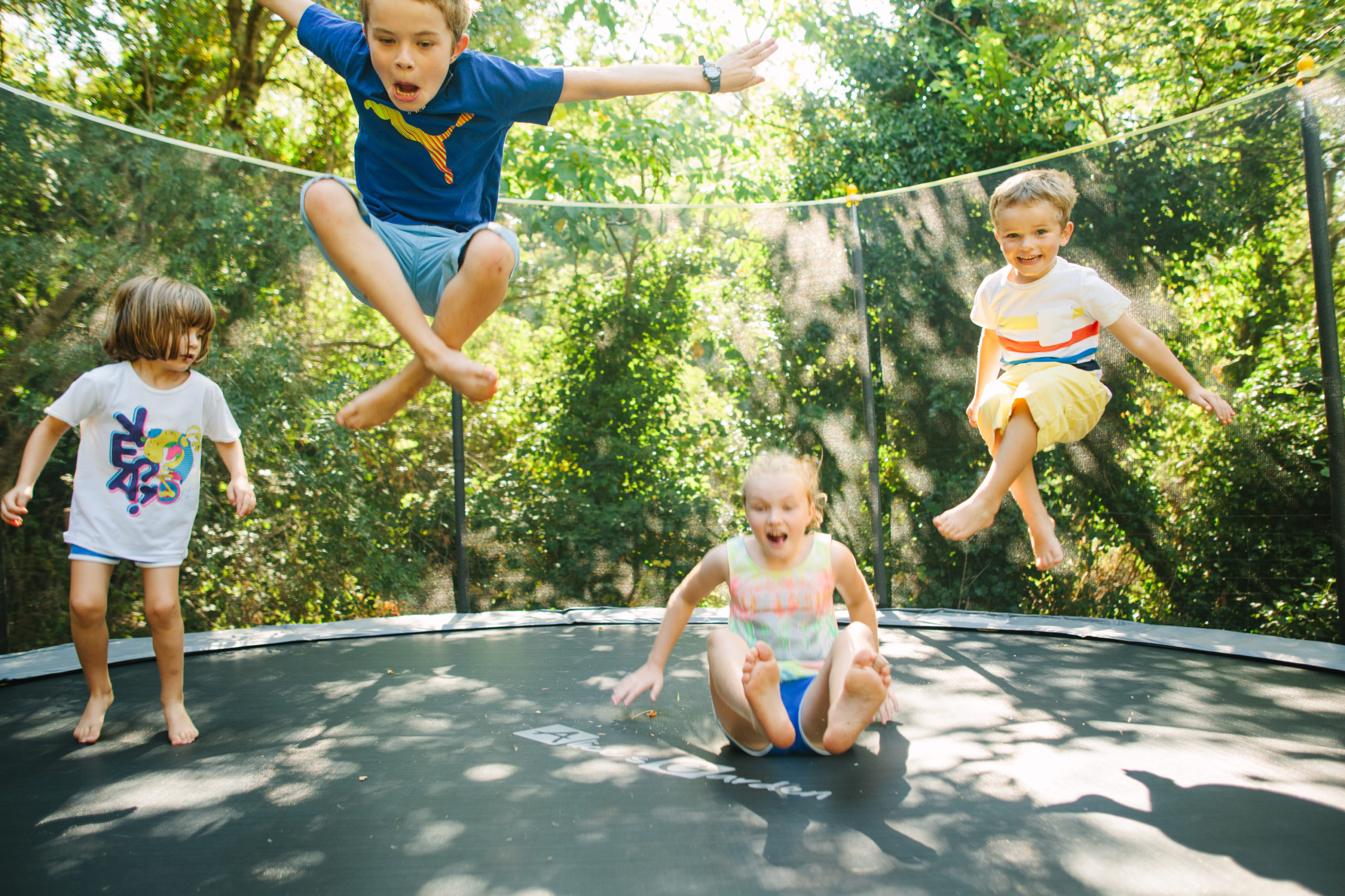 Kids jumping on a trampoline, south of France weekend break, Country kids